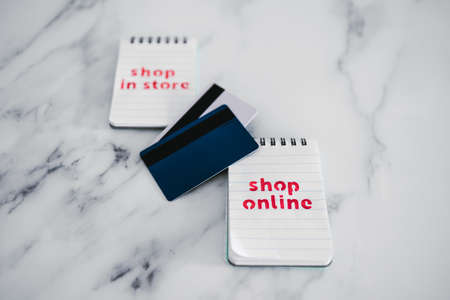 competition and retail industry conceptual image, shop in store vs shop online texts on notepads with payment cards next to them