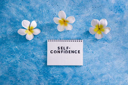 positive attitude concept, Self-confidence text on notepad with tropical flowers around it on blue background
