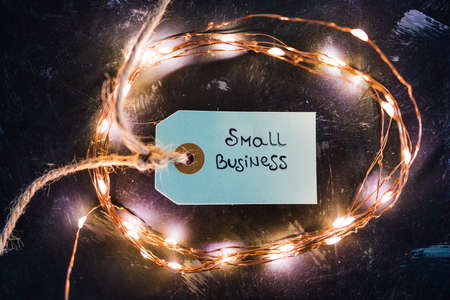 product tags with small business text surrounded by fairy lights, concept of customer behaviour and supporting small businesses and locally made items