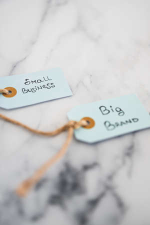 product tags with small business vs big brand texts with focus on the small one, concept of customer behaviour and supporting small businesses and locally made items