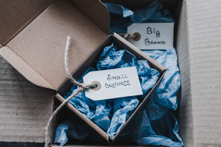 product tags with small business vs big brand texts inside of bigger and smaller delivery parcels, concept of customer behaviour and supporting small local businesses