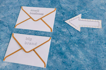 small business vs big brand texts over newsletter email envelopes with arrow pointing towards the small one, concept of customer behaviour and supporting small local businesses