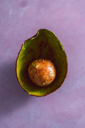 half empty avocado with pulp removed and only pip and skin remaining shot as close-up on pink background