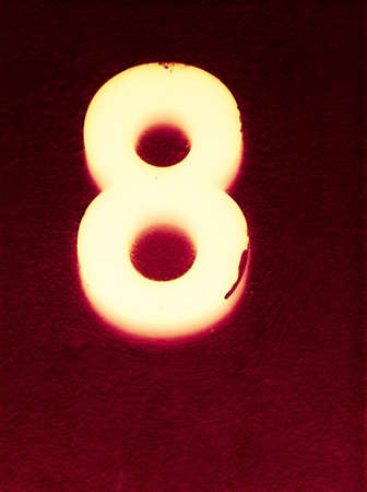 glow: Number eight glowing in the dark Stock Photo