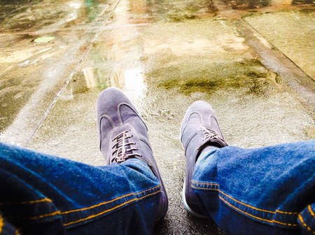 denim: Men with denim and shoes waiting in the rain Stock Photo