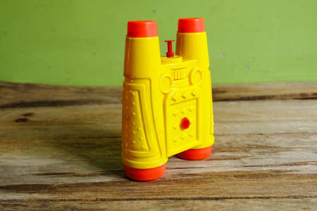Selective focus of binocular type of water gun toys for kids on wooden background.