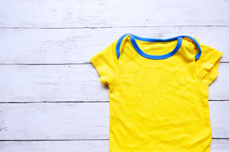 Top view of yellow and blue baby romper on white wooden background. Copy space for text or graphic.