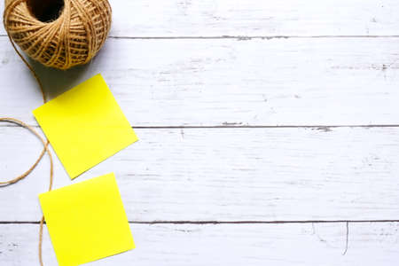 Miscellaneous theme. Top view of three empty yellow sticky notes and brown rope on wooden background. Copy space for text or logo.