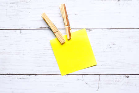 Miscellaneous theme. Top view of empty yellow sticky notes and cloth pegs on wooden background. Copy space for text or logo.