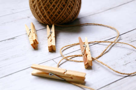 miscellaneous theme. Close up view of cloth pegs and brown rope on white wooden background.