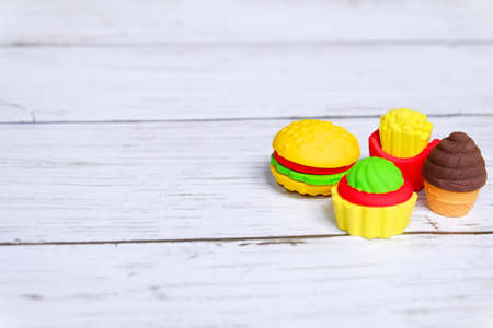 Concept of fast food of burger,french fries,and cake in kids eraser form on wooden background with copy space for text or logo.