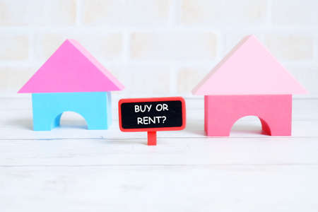 Selective focus of red blackboard written with BUY OR RENT? with house model on white wooden background. Real estate theme. Stockfoto