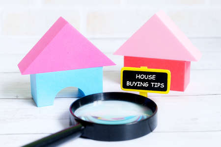 Selective focus of yellow blackboard written with HOUSE BUYING TIPS with house model and magnifying glass on white wooden background. Real estate theme.
