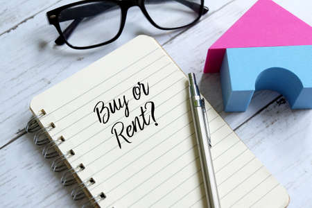 Sunglasses,home model,pen and notebook written 'BUY OR RENT?' on white wooden background. Banque d'images