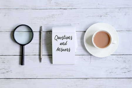 Top view of a cup of coffee,magnifying glass,pen and notepad written with 'QUESTIONS AND ANSWERS' on white wooden background.