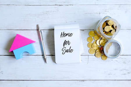 Top view of a jar of coins,home model,pen and notebook written with HOME FOR SALE on white wooden background.