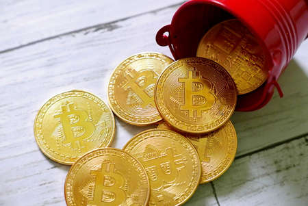 Golden Bitcoin replica fall from red pile on white wooden background. Business and finance concept. Stock Photo