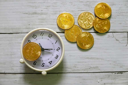 A golden replica of bitcoin with clock on white wooden background.Business and finance concept.