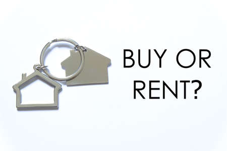 Real estate or property theme. House key chain on white background written with question BUY OR RENT?