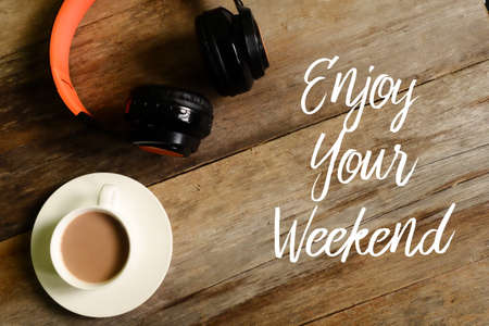 Top view of headphones and a cup of coffee on wooden background written with ENJOY YOUR WEEKEND
