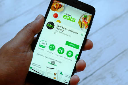 BANDAR SERI BEGAWAN,BRUNEI - JULY 25TH,2018 : A male hand holding smartphone with Uber eats app on an android Google Play Store.