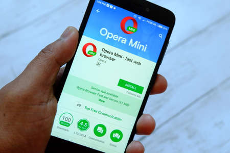 BANDAR SERI BEGAWAN,BRUNEI - JULY 25TH,2018 : A male hand holding smartphone with Opera Mini app on an android Google Play Store