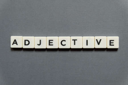 Adjective word made of square letter word on grey background.