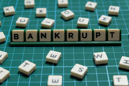 Bankrupt word made of square letter word on green square mat background. Stockfoto