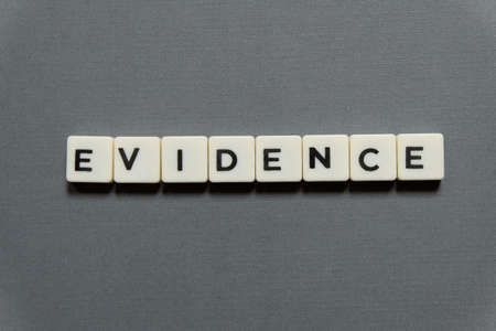 Evidence word made of square letter word on grey background.