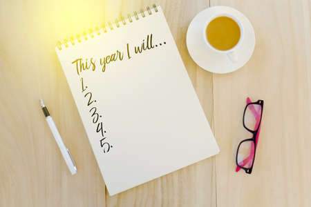 Top view of pen,coffee,sunglasses and notebook written with This Year I Will... New Year concept with copy space Imagens