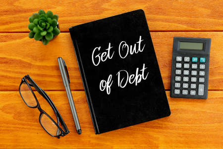 Top view of eyeglasses,calculator,plant,pen and notebook written with Get Out Of Debt on wooden background. Business and finance concept.