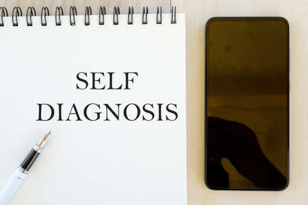 Health concept.Top view of mobile phone,pen and notebook written with Self Diagnosis.