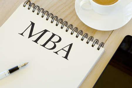 Bildungskonzept. Handy, eine Tasse Kaffee, Stift und Notizbuch mit MBA geschrieben.