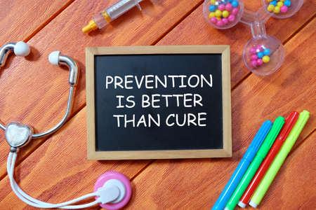 Medizin- und Gesundheitskonzept. Draufsicht auf Spielzeug-Stethoskop, bunten Stift, Spritze und Tafel geschrieben mit Prävention ist besser als Heilung auf Holzhintergrund.