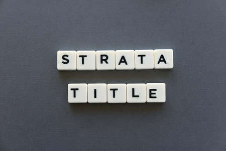Strata title word made of square letter word on grey background.