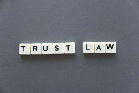 Trust law word made of square letter word on grey background.
