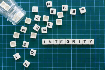 Integrity word made of square letter word on green background.