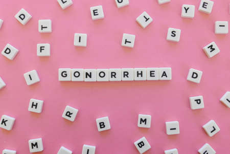 Gonorrhea word made of square letter word on pink background.