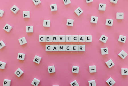 Cervical cancer word made of square letter word on pink background.