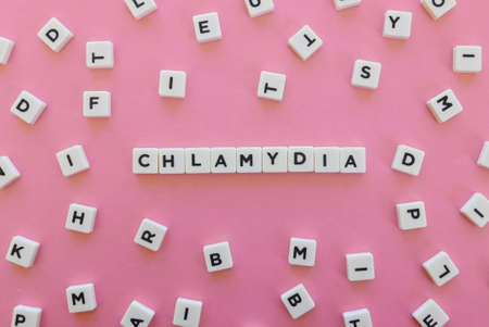 Chlamydia word made of square letter word on pink background.