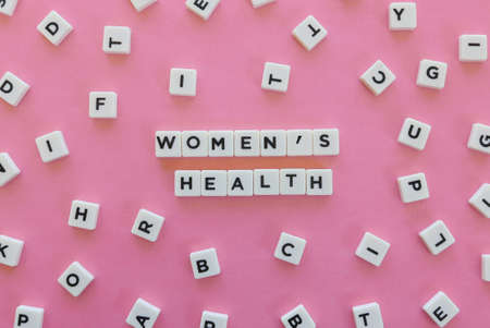 Womens Health word made of square letter word on pink background.