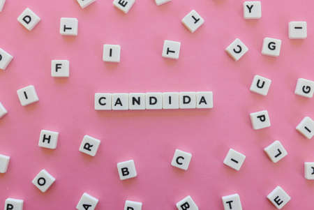 Candida word made of square letter word on pink background. Stock Photo