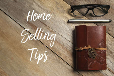 Top view of pen,glasses and notebook on wooden background written with Home Selling Tips.