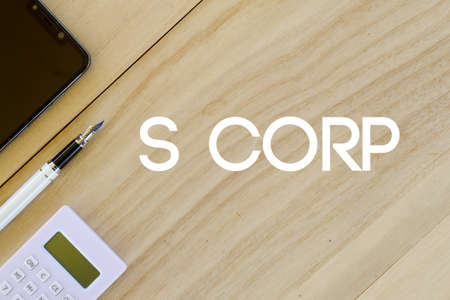Top view of mobile phone,pen and calculator on wooden background written with S Corp. Business and finance concept.