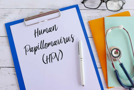 Top view of books,stethoscope,glasses,pen,clipboard and paper written with Human Papillomavirus (HPV). Healthcare and medical concept.