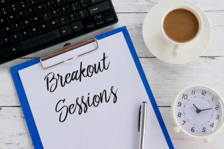 Top view of keyboard,coffee,clock,pen,clipboard and paper written with Breakout Sessions. Imagens - 118841540