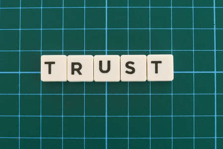 Trust word made of square letter word on green square mat background.