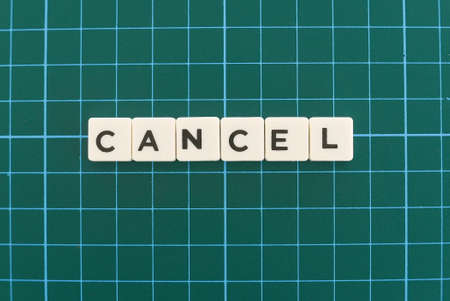 Cancel word made of square letter word on green square mat background.