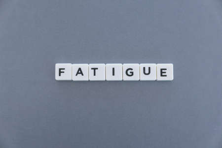 Fatigue word made of square letter word on grey background. 免版税图像