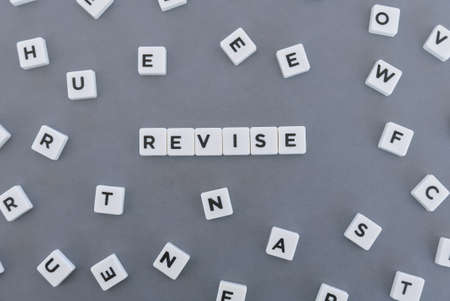 Revise word made of square letter word on grey background. Imagens